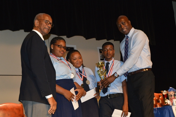 Debators from Claudia Creque Educational Centre collect their trophy from Premier Dr D Orlando Smith (left) and Minister of Education Myron Walwyn